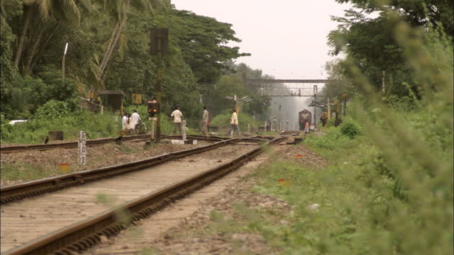 MS POV People crossing railway track /  Kerala, India