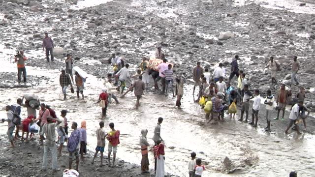 People crossing river after bridge fell down