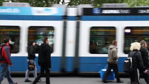 ms pan people crossing street after moving tram / zurich, switzerland - commercial land vehicle stock videos & royalty-free footage