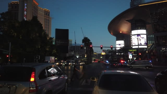 people crossing street and police cars rushing in las vegas at twilight - police vehicle lighting stock videos & royalty-free footage