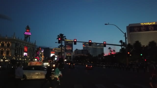 people crossing street and volcano erupts show at the mirage hotel in las vegas at twilight - las vegas crosses stock-videos und b-roll-filmmaterial