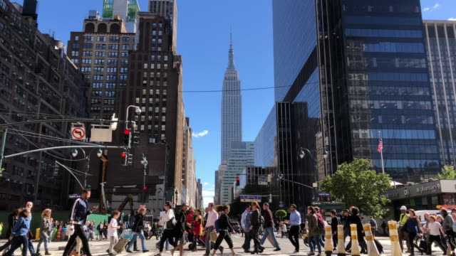 people crossing street in new york city with empire state building in the background - fußgänger stock-videos und b-roll-filmmaterial