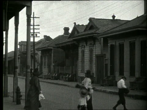 vídeos y material grabado en eventos de stock de b/w people crossing street with small houses / new orleans / 1915 / no sound - 1910