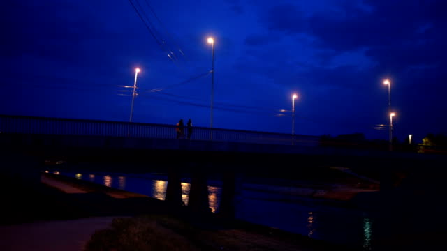 夜明けに橋を渡る人々