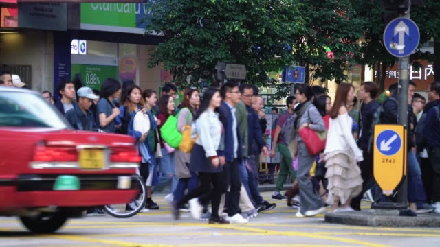 vidéos et rushes de personnes qui traversent la route à hong kong - chinois