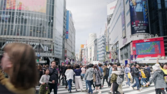 people crossing the shibuya crossing in japan - road junction stock videos & royalty-free footage