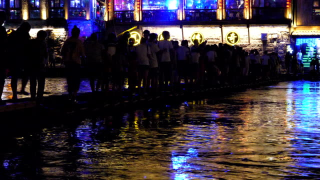 People crossing the Tuo Jiang River in Fenghuang at night