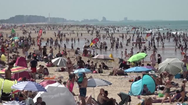 people crowd ostend beach in belgium where the temperature reaches 34 degrees celsius as swathes of western europe wilt under intense heat - western europe stock videos & royalty-free footage