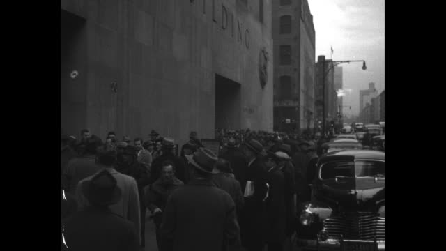 people crowd sidewalk in front of federal office building traffic moving on street / man holding up daily news newspaper with huge headline reading... - formationsfliegen stock-videos und b-roll-filmmaterial