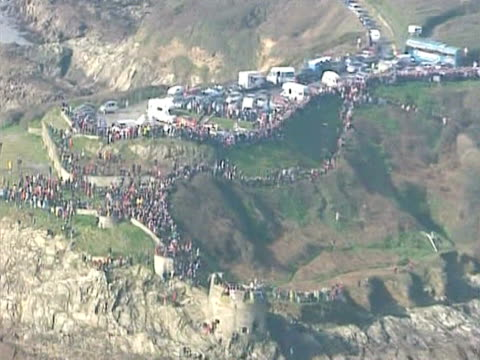 People crowd the cliffs near Falmouth harbour to welcome back Ellen Macarthur after she successfully breaks the world record for sailing solo around...