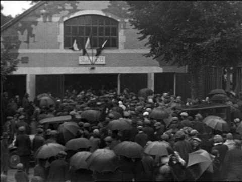 view people crowding around building / some with umbrellas / france / docu - anno 1925 video stock e b–roll