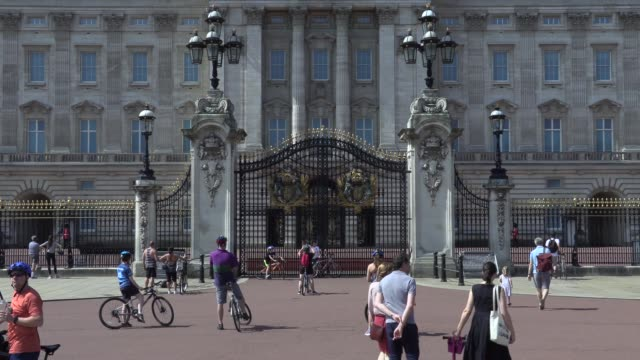 people cycle around green park and stop to look at buckingham palace on a hot bank holiday weekend in london boris johnson is expected to announce... - smooth stock videos & royalty-free footage