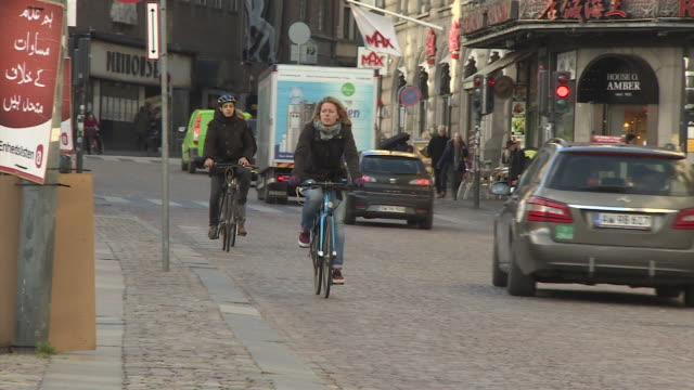 people cycle down a road in central copenhagen. - copenhagen stock videos and b-roll footage