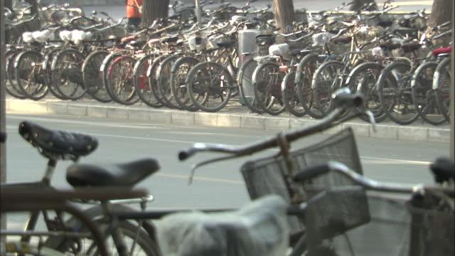 vídeos y material grabado en eventos de stock de people cycle past cycle racks, beijing, china - manillar