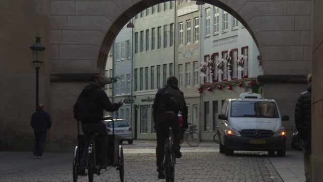 people cycle underneath a stone archway in central copenhagen. - copenhagen stock videos and b-roll footage