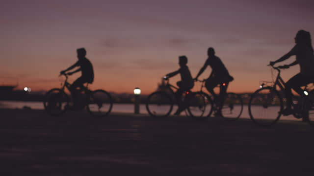 people cycling, jogging, walking at sunset near the sea out of focus - silhouette stock videos & royalty-free footage