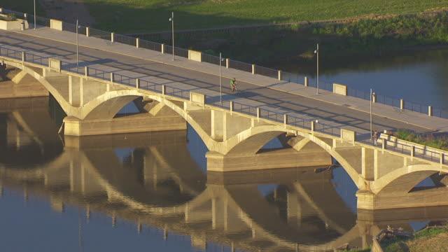 vídeos de stock e filmes b-roll de ws pan aerial pov people cycling on bridge over river / des moines, iowa, united states - des moines iowa