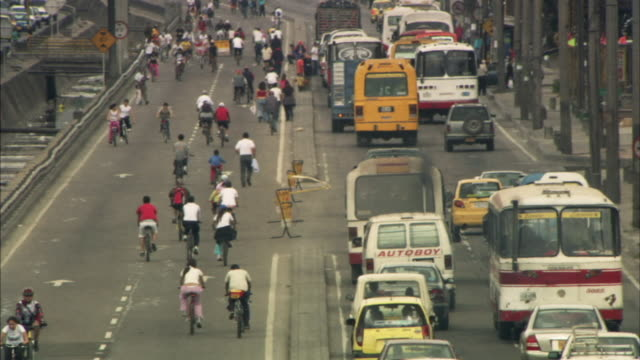 HA WS People cycling, walking, and driving in traffic on busy street / Bogota, Colombia