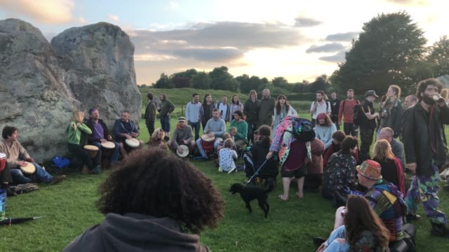 vídeos y material grabado en eventos de stock de people dance at avebury neolithic henge monument, a unesco world heritage site, as the sun begins to set on june 20, 2018 in wiltshire, england.... - solsticio de verano