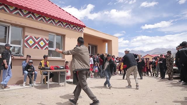 people dance during a wedding in front bride's home on june 20 in kashgar, xinjiang uygur autonomous region of china. - 新疆ウイグル自治区点の映像素材/bロール