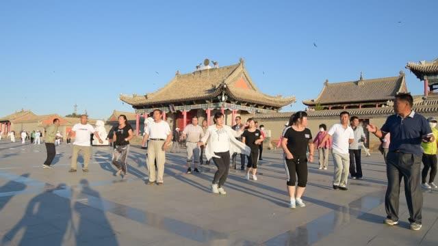 vídeos y material grabado en eventos de stock de people dance in public in front of an old temple in xilinhot inner mongolia china on july 17 2018 - grupo grande de personas