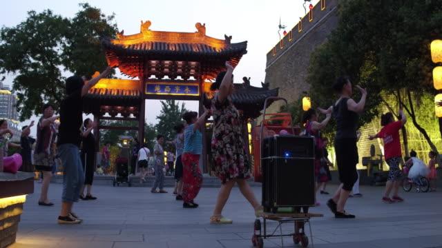 vídeos de stock e filmes b-roll de people dance in public near the ancient city wall on june 17, 2017 in xi an, china. - dança quadrada