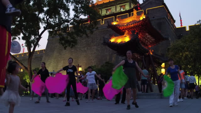 People dance in public near the ancient city wall on June 17 2017 in Xi An China Xi'an is one of the oldest cities in China it is the oldest of the...