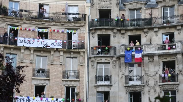"""people dance on the balcony of their apartments where words """"dance at home"""" and """"take care of yourself"""" are written on a banner in support of... - balcony stock videos & royalty-free footage"""