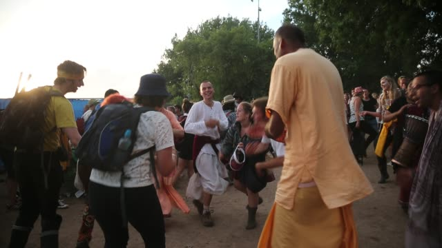 People dance with members of the Hare Krishna movement at the Glastonbury Festival at Worthy Farm Pilton on June 27 2015 in Glastonbury England