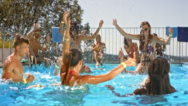 SLO MO DS People dancing and laughing in the water at a pool party on a hot day