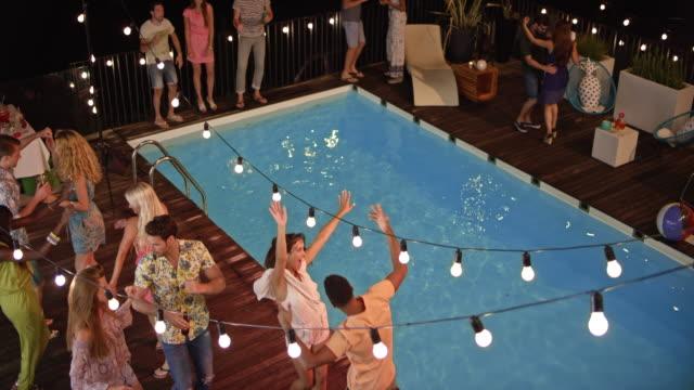 cs persone che ballano e parlano a una festa a bordo piscina la sera - swimming pool video stock e b–roll