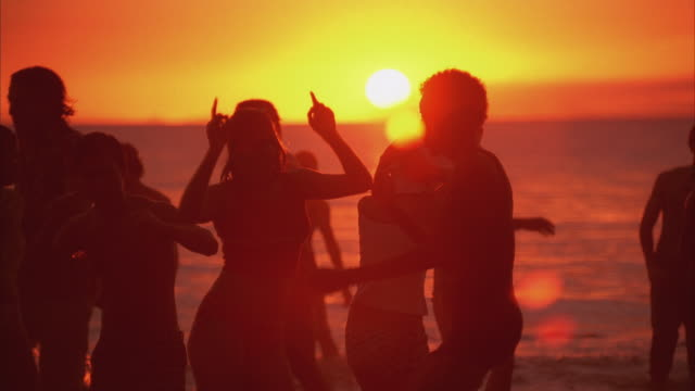 ws people dancing at ocean's edge at sunset - inflatable stock videos & royalty-free footage