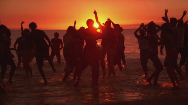 WS People dancing at ocean's edge at sunset