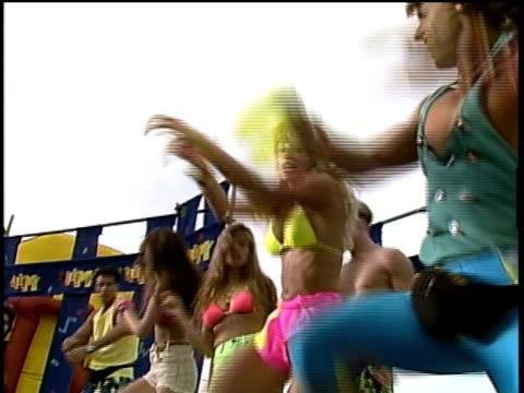 vidéos et rushes de people dancing at spring break party on beach - couleur fluo