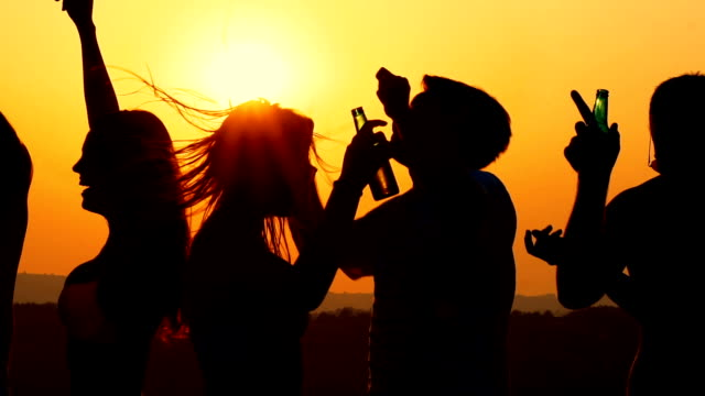people dancing at sunset, slow motion. - controluce video stock e b–roll