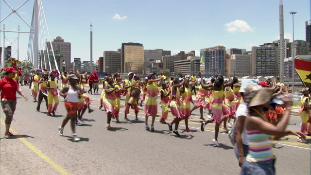 ws zi people dancing during soccer parade through city street / johannesburg, gauteng, south africa - republik südafrika stock-videos und b-roll-filmmaterial
