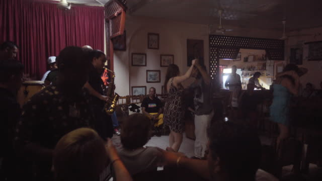 People dancing in a Cuban Club with live music named Casa de la Trova. Tourists learning from local people.