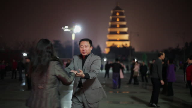 MS People dancing in front of big wild goose pagoda  AUDIO  / xi'an, shaanxi, china
