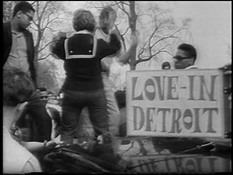 vídeos de stock e filmes b-roll de b/w 1967 people dancing next to lovein detroit sign outdoors / belle isle / newsreel - love in