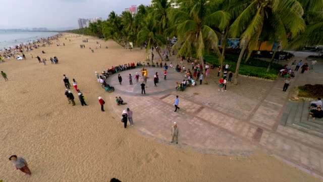 people dancing on beach in sanya, hainan province, china. drone shot - spoonfilm stock-videos und b-roll-filmmaterial