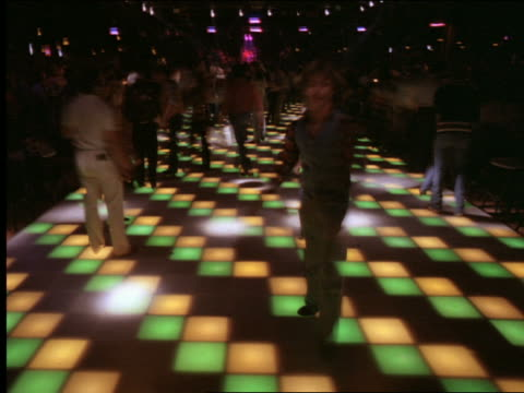 T/L people dancing on multi colored dance floor in disco
