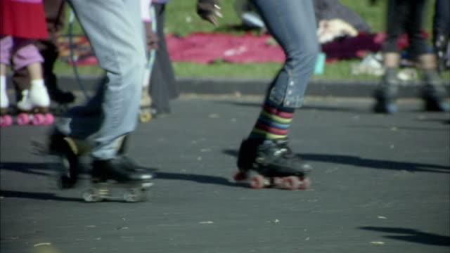 CU People dancing on roller skates on park path, San Francisco, California, USA