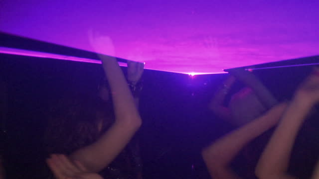 vidéos et rushes de ms slo mo people dancing under laser lighting in nightclub, london, england, pan - angleterre