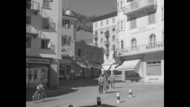 People descend boarding stairs from a Trans World Airlines airplane / a quaint Swiss village square / high angle view of a roulette table with people...