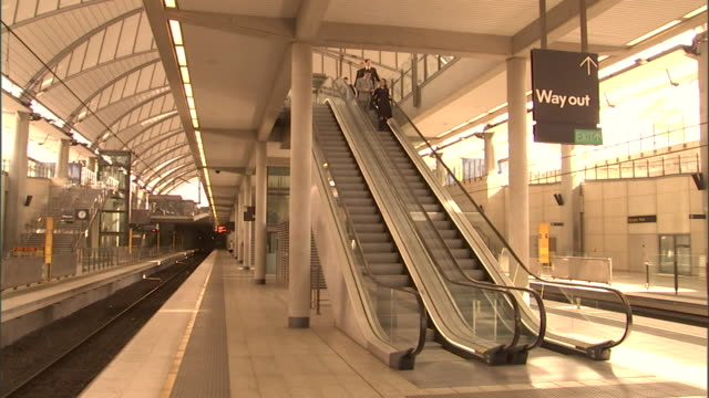 ms, people descending escalator and waiting for train on platform, olympic park railway station, sydney, australia - escalator stock videos & royalty-free footage