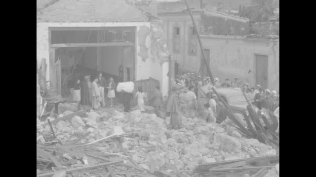 vidéos et rushes de vs people digging though rubble of collapsed cinderblock structures people in ruins of convent bed seen though hole in wall people milling around... - parpaing