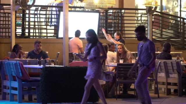 people dining outdoors at 411 south bar grill on fort lauderdale beach boulevard as pedestrians some wearing protective face coverings walk by on... - scott mcpartland stock videos & royalty-free footage