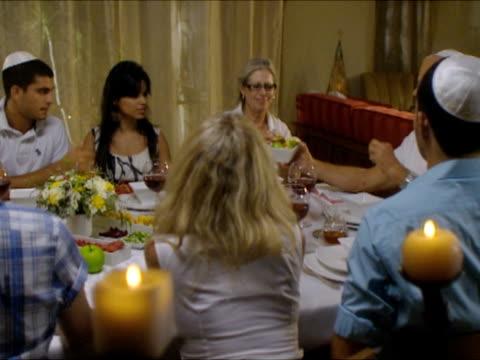 ms pan people dipping apples in honey sitting around dinner table during rosh hashanah / beit yitzhak, israel - rosh hashanah stock videos & royalty-free footage