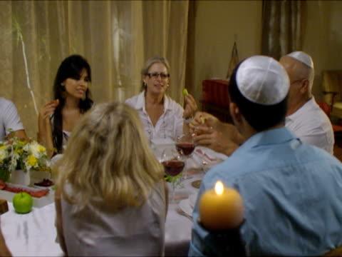 vidéos et rushes de ms pan people dipping apples in honey sitting around dinner table during rosh hashanah / beit yitzhak, israel - judaism