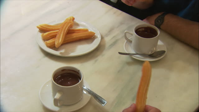 ms people dipping churros in chocolate, madrid, spain - churro stock videos & royalty-free footage